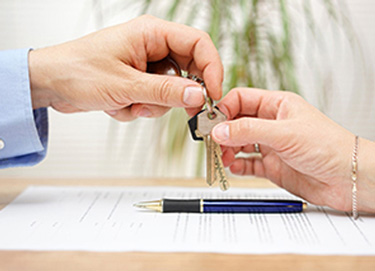 person handing over keys to another person