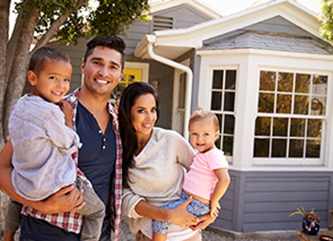family smiling and standing in front of house