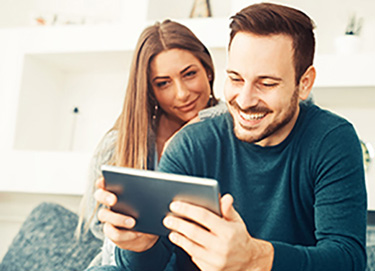 man and woman smiling at tablet