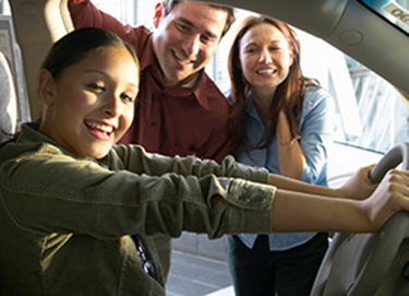 parents smiling at teen in car