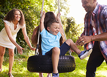 man and woman pushing children on tire swing